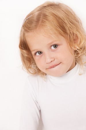 Blonde little girl dressed in white biting her lip on  white background photo