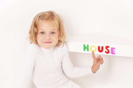 Blonde little girl dressed in white stuck word  house of colorful letters  on the shelf Stock Photo - 10284767
