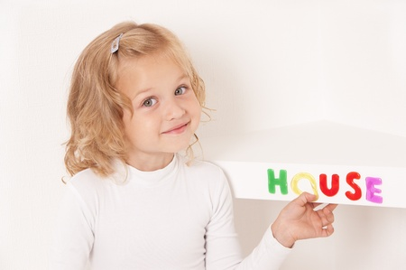 Blonde little girl dressed in white stuck word  house of colorful letters  on the shelf photo