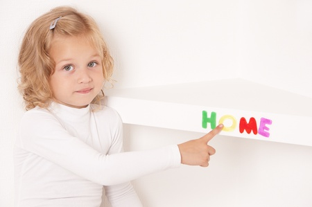 Blonde little girl dressed in white stuck word  home of colorful letters  on the shelf