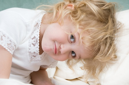 Adorable little girl resting in the bed close-up photo