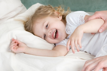 Laughing adorable little girl resting in the bed