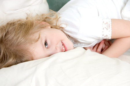 Laughing adorable little girl resting in the bed photo