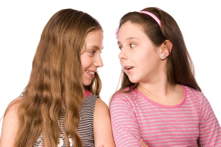 grinning: Two girls in the age of ten and eleven talking isolated on white