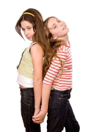Two girls in the age of ten and eleven standing and embracing hands isolated on white