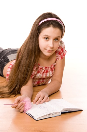 Pretty girl in the age of eleven making notes on diary on the floor on white  Stock Photo