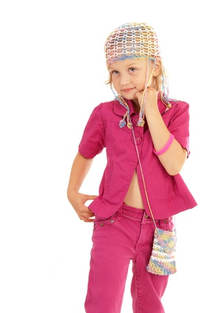 Little girl dressed in a pink dress posing for the camera on white background