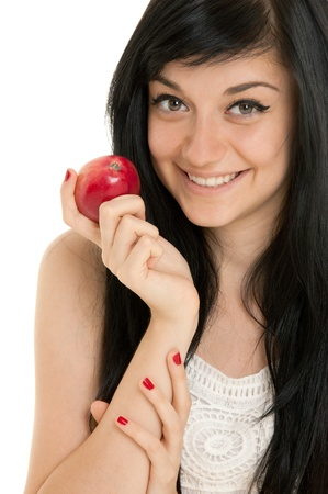 Beautiful brunette girl wearing a white dress putting red apple and standing on white background Stock Photo