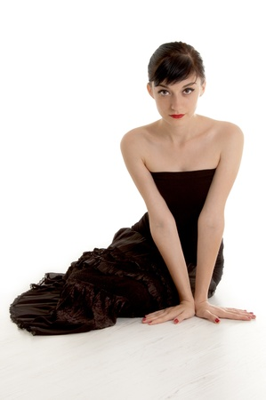 Beautiful  brunette girl wearing a black dress sitting on the floor and  looking directly at the camera on white background Stock Photo