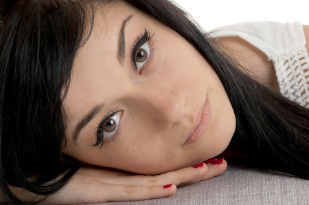 Beautiful brunette girl lying on the gray cushion  close-up