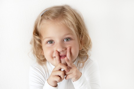 Blonde little girl  dressed in white standing and puts her fingers to her mouth in the form of letters H photo