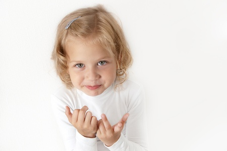Blonde little girl  dressed in white looking directly at the camera on a white background