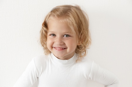 Blonde smiling little girl  dressed in white looking directly at the camera on a white background
