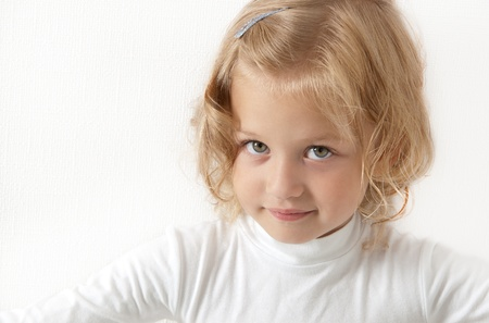 Blonde little girl  dressed in white looking directly at the camera on a white background photo
