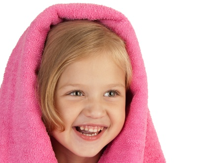 Smiling little girl wrapped in a pink towel close-up photo