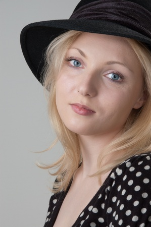 Young beautiful sexy  blonde woman in a black hat looking at camera close-up