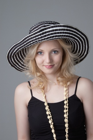 Young beautiful smiling  blonde woman in a hat  and a black dress looking and posing for the camera  Stock Photo