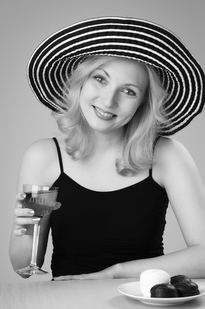 Young beautiful laughing  blonde woman in a hat  looking and posing with a glass of wine for the camera photo