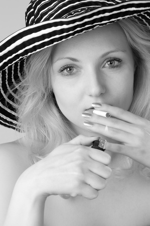 Young beautiful  blonde woman in a hat smoking, looking and posing for the camera close-up photo