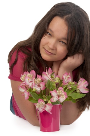 Asian smiling girl at the age of twelve  with pink flowers looking at the camera on white Banco de Imagens
