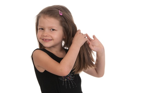 Cute smiling girl at the age of five standing with her hands raised to the hair on a white background