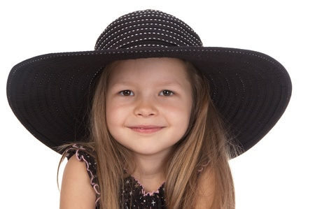 Cute smiling girl at the age of five in big black hat on white background