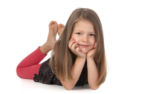 Cutesmiling girl at the age of five lying on the floor and looking at the camera on white background