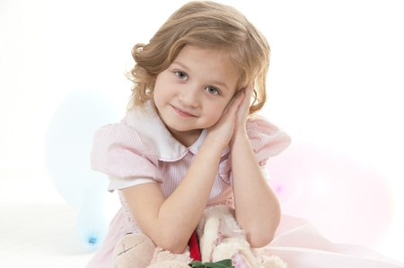 Smiling adorable little blonde girl at the age of five wearing a pink dress looking  at the camera on a white background Stock Photo - 13952452