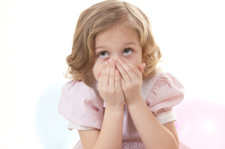 Scared adorable little blonde girl at the age of five wearing a pink dress covers her face and looks up on a white background Stock Photo - 13952455