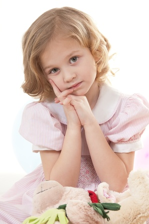 Sad adorable little blonde girl at the age of five wearing a pink dress looking  thoughtfully into the camera sitting on the floor on a white background