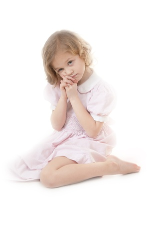 Sad adorable little blonde girl at the age of five wearing a pink dress sitting pensively on a white background Stock Photo - 13952451