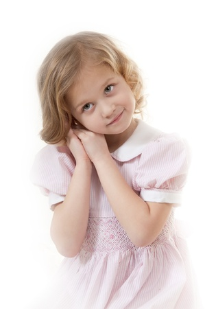 Smiling adorable little blonde girl at the age of five wearing a pink dress looking  thoughtfully on a white background Stock Photo - 13952456