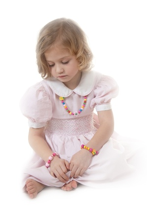 Sad adorable little girl at the age of five wearing a pink dress looking down thoughtfully on white background Stock Photo - 13952450