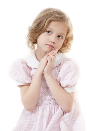Sad adorable little blonde girl at the age of five wearing a pink dress looking  thoughtfully on a white background