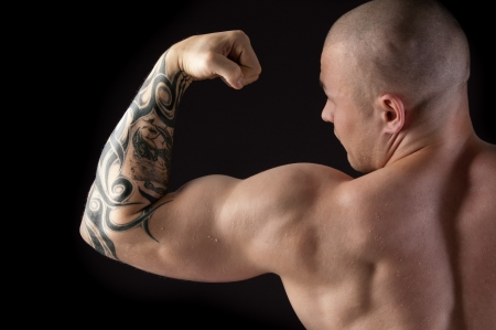 Strong man with relief body and a tattoo on his arm
