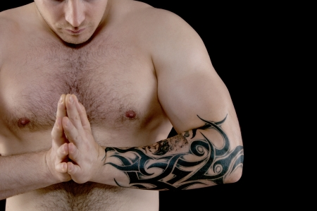 Muscular man with a tattoo on his arm flexing his biceps photo