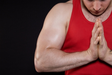 Muscular man in a red T-shirt flexing his biceps close-up Banco de Imagens