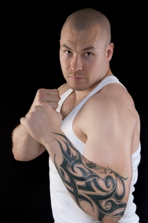 Muscular man body with a tattoo on his arm looking at the camera