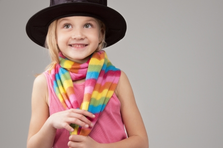 Smiling six year old girl in a black hat and a colorful scarf looking up standing on a gray background Stock Photo - 16763872