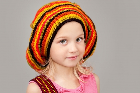 Adorable smiling little girl in colorful striped knitted cap looking at the camera close-up Stock Photo - 16796339