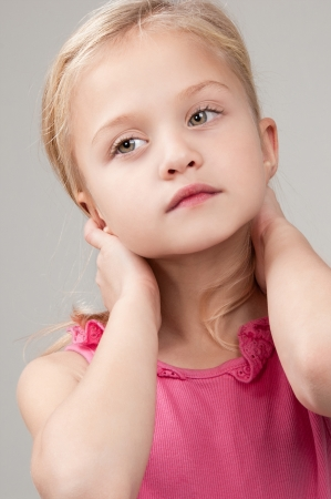 Blonde adorable little girl in pink T-shirt looking pensively close-up Stock Photo - 16796334