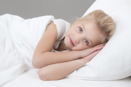 cute little girl resting in the bed with his hands behind his head on a white pillow and looking at the camera