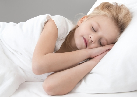 cute little girl sleeping with his hands behind his head on a white pillow