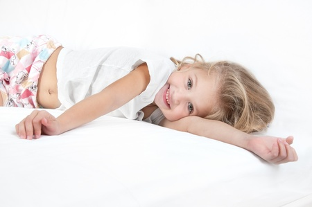Adorable little girl resting in bed and looking at the camera close-up