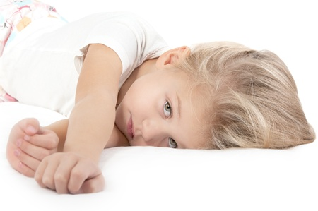 tired face: Adorable little girl resting in bed and looking at the camera close-up on white Stock Photo