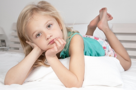 Adorable little girl looking at the camera with his arms crossed behind his head close-up