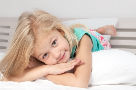 Adorable little girl looking at the camera with his arms crossed behind his head close-up Stock Photo - 16824500