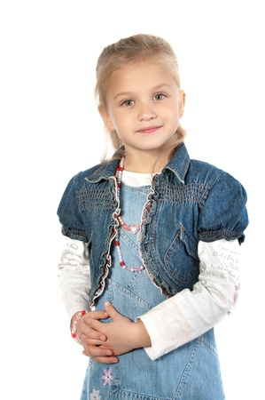 Adorable smiling little giirl wearing a jean dress and jacket standing with folded hands on waist and looking at the camera white background