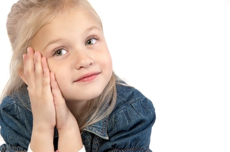 Adorable smiling little giirl wearing a jean jacket sitting put her hands to the face and looking thoughtfully on white background close-up Stock Photo - 16824501