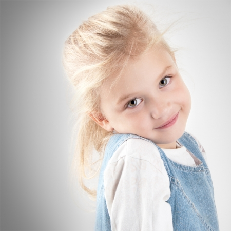 Adorable smiling little giirl wearing a jean dress standing  looking at the camera close-up Banco de Imagens